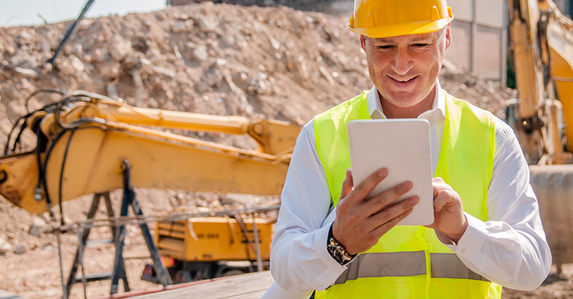 Construction worker on site using a tablet
